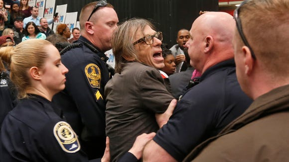 Photojournalist Christopher Morris is escorted by police