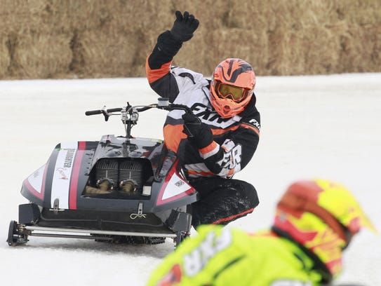 A racer makes a hand gesture as the race ends during