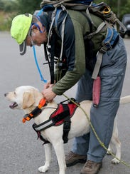 Tom Henning puts a GPS collar on Sahale during a K9