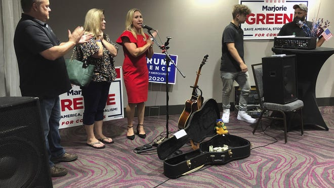 Construction executive Marjorie Taylor Greene, third from left, claps with her supporters at a watch party event, late Tuesday, Aug. 11, 2020, in Rome, Ga. Greene, criticized for promoting racist videos and adamantly supporting the far-right QAnon conspiracy theory, won the GOP nomination for northwest Georgia's 14th Congressional District.