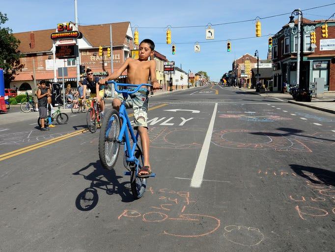Jose Morales, 11, of Detroit pops a wheelie on his