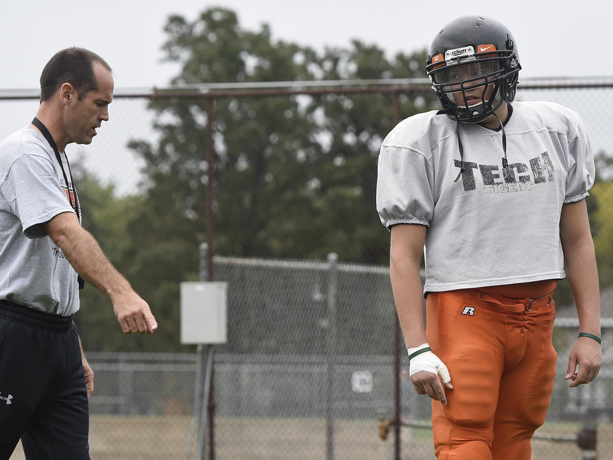 St. Cloud Tech's Jonathan Karels works with coach Greg Martig Wednesday during practice at Clark Field.