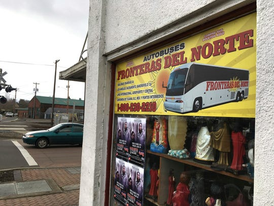 In this March 2, 2017, photo shows a sign advertising bus trips to California with connections to Mexico, at a shop in the predominantly Latino town of Woodburn, Ore. Federal immigration agents recently detained people in the town. Farmers, nursery and winery owners and others who depend on immigrant labor are predicting a catastrophe as federal immigration agents focus on stepping up arrests of people who are in America illegally.