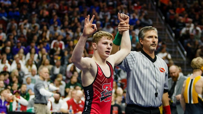 Fort Dodge's Brody Teske raises a three after winning his third state championship at his class 3A 120 pound championship match at the Iowa high school state wrestling tournament on Saturday, Feb. 18, 2017 in Des Moines.