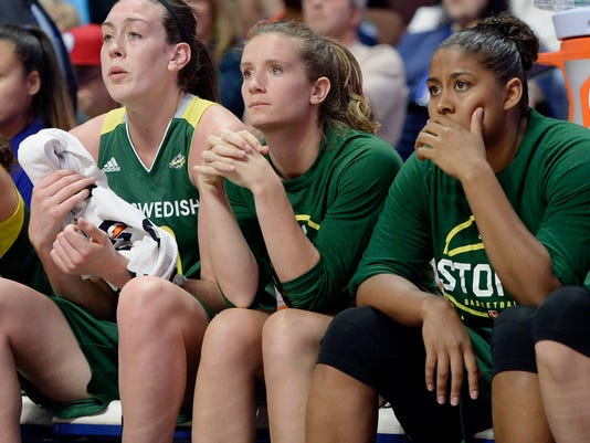 In this June 10, 2016, photo, former Princeton player Blake Dietrick sits on the bench between Seattle Storm teammates Breanna Stewart, left, and Kaleena Mosqueda-Lewis, right, during the first half of a WNBA basketball game against the Connecticut Sun in Uncasville, Conn. (AP Photo/Jessica Hill)