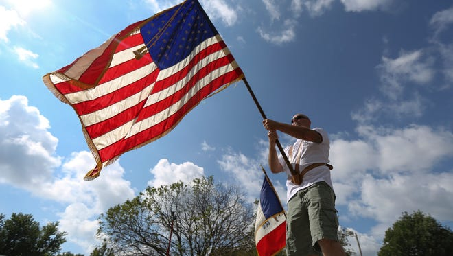 A man carries the American flag during the annual Labor Day parade on Sept. 1, 2014, in Des Moines.