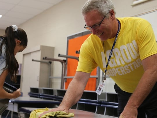 Scales Elementary School fifth-grade teacher Steve Nagy cleans a desk in his classroom on the last day of school on Thursday