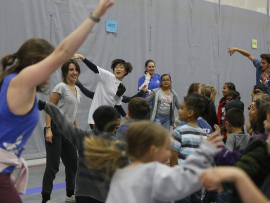 Members of Up with People teach a dance to kids at