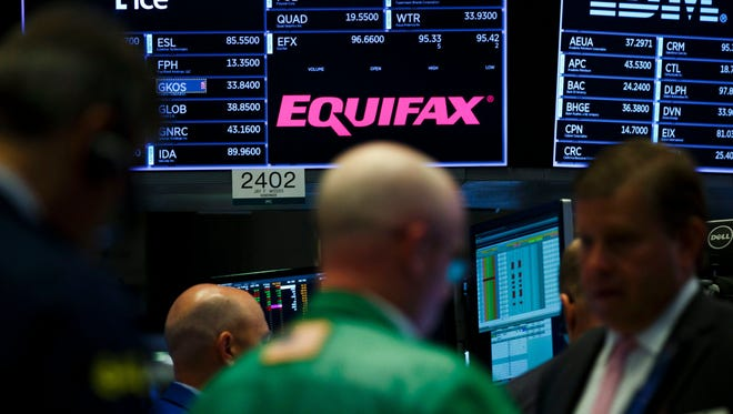 File photo taken in Sept. 2017 shows a sign for credit-reporting company Equifax on the floor of the New York Stock Exchange.