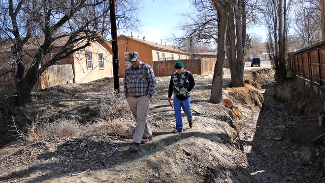 Jim DeAngelo, left, a mitigation project leader with AECOM, and Sherrick Campbell, a water resource engineer, walk along the Blanco Arroyo near East Blanco Street in Aztec on Feb. 24.