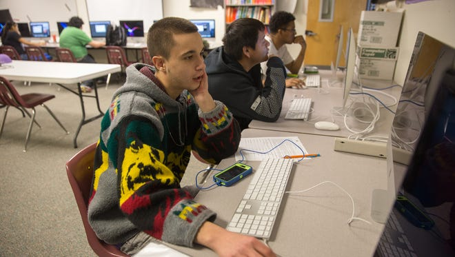 Seniors Jacob Sharp, left, Augustin Blackwater and Jenecio Avalos work in the computer lab Tuesday at Rocinante High School in Farmington, which saw a large increase in its graduation rate for the 2015-2016 school year.