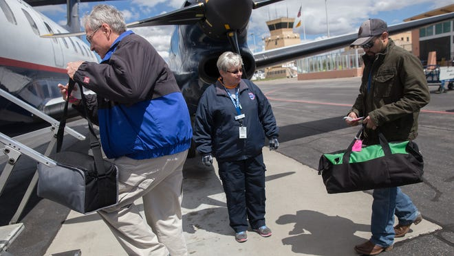 Debbie Meador, the station manager for Great Lakes Airlines, assists passengers Thursday as they board a Great Lakes Airlines flight at the Four Corners Regional Airport in Farmington.