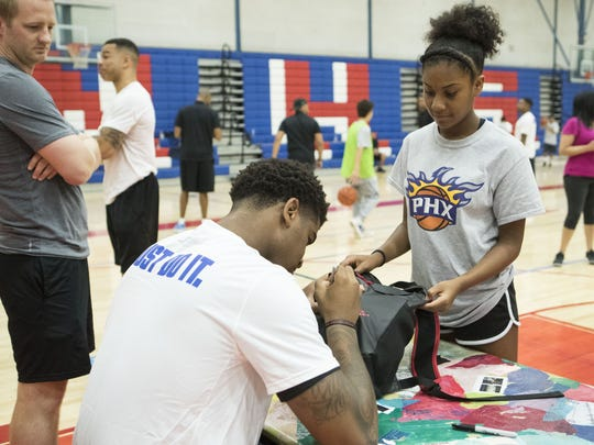 Phoenix Suns' Marquese Chriss signs 13-year-old May Moody's backpack at North High School on Aug. 13, 2017 in Phoenix.