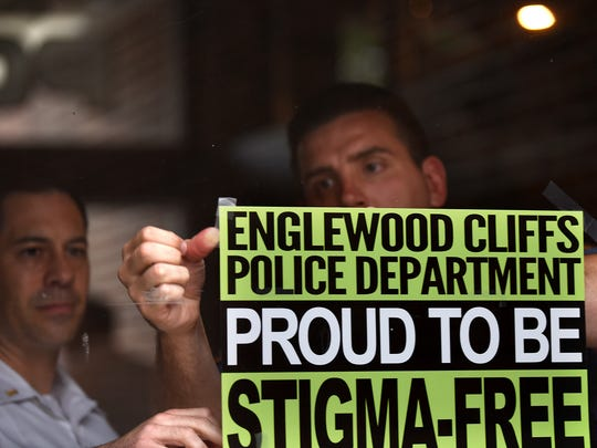 "Englewood Cliffs Police Department goes stigma free. Lt. William Henkelman and Daniel O'Shea put up a ""Stigma-Free"" sign on the door to the Englewood Cliffs Police Department on Tuesday July 03, 2018."