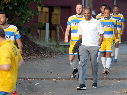 Kitsap Pumas coach Roy Lassiter walks with his team at halftime during a game against FCM Portland at Gordon Field last week.