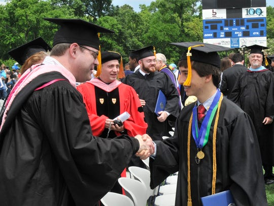 Fifteen year old Keith Harding, right, greets people after Faulkner University Commencement Ceremony at the Billy D. Hilyer Stadium on Friday, May 2, 2014, in Montgomery, Ala..