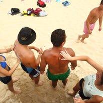 Beach-goers apply sunscreen to each other at Bondi Beach