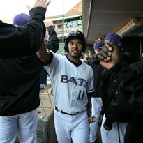 Louisville's Ivan De Jesus Jr. (11) high fives players in the dug out after scoring a run while playing the Toledo Mud Hens at Louisville Slugger Field in Louisville, Ky. April 11, 2015.