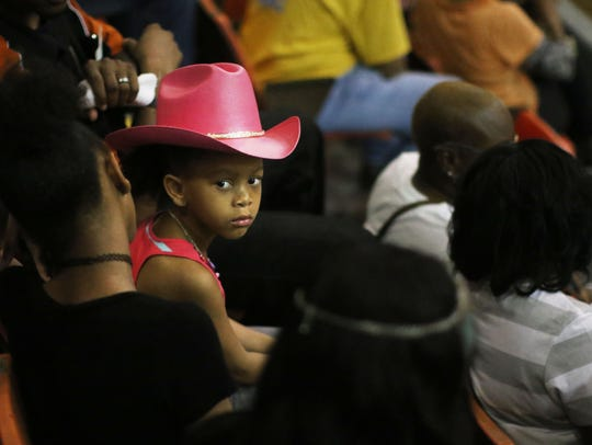 Lyla Roberson, 4, sits with her family as they wait