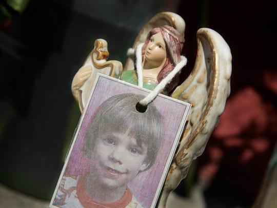 A photograph of Etan Patz hangs on an angel figurine,