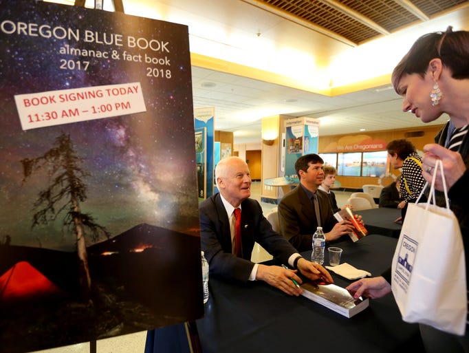 Secretary of State Dennis Richardson signs a copy of