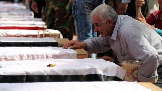 An Iraqi man mourns on June 2, 2015, next to the coffins of Iraqi soldiers killed in a suicide attack by the Islamic State in northern Ramadi the day before.