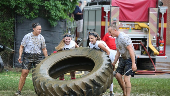 A co-ed team tries to flip an over-sized tire on an obstacle course in Friday's Rancocas Valley Red Devil Dash at the regional high school in Mount Holly to benefit military causes and students entering the military. More than 800 students and community members competed.