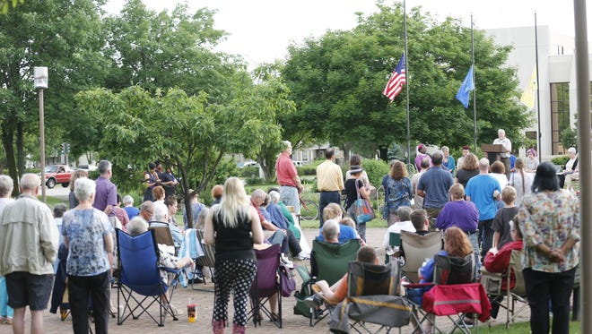 People gathered Wednesday evening in Veterans Park in Fond du Lac to remember the 49 victims in the Orlando, Florida, shooting. Hanging along the stage were rainbow and transgender flags. Behind the stage, the United States and other flags were at half-mast.