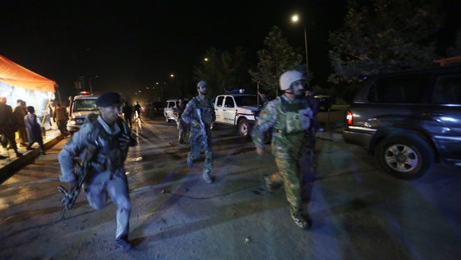 Afghan security forces rush toward the campus of the American University in the Afghan capital Kabul on Aug. 24, 2016.