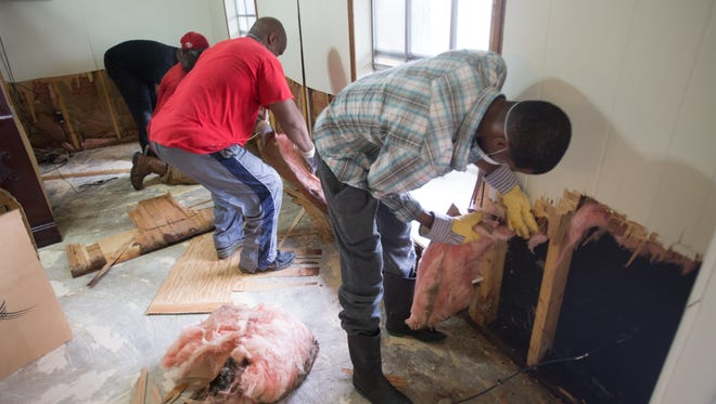 Family members tear out insulation from a flood-damaged in the Derby Heights neighborhood of Lafayette August 28, 2016.