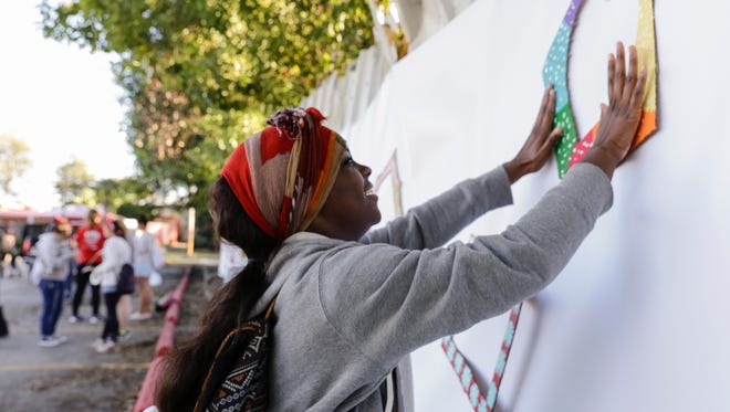 Tyrica James places a heart-shaped frame on a wall during Better Block McKinley, a one-day transformation of McKinley Street into a two-way pedestrian friendly street in Freetown Oct. 22, 2016, in Lafayette.