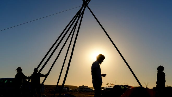 Campers at Oceti Sakowin build a tipi as the sun begins to set over the campground near Cannon Ball N.D. on Saturday, Nov. 12, 2016.