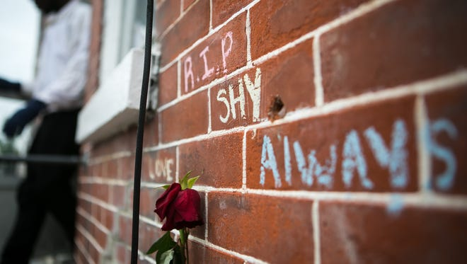 A rose and messages are left on the front brick wall of the home where 16-year-old Tynesia Cephas died on Kirkwood Street in Wilmington.