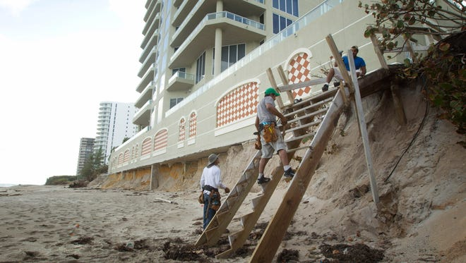 Construction workers at Ocean Edge condo on Singer Island, Fla., rebuild a walk to the beach on Nov. 29, 2012, after Superstorm Sandy and heavy waves washed away the sand from under the building.