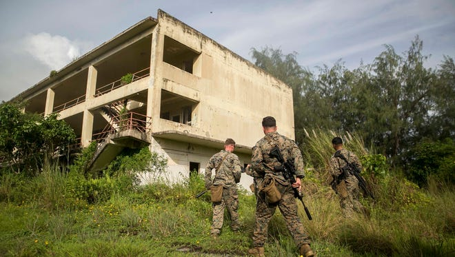 Marines with Battalion Landing Team, 3rd Battalion, 5th Marines, enter an abandoned building during Military Operations in Urbanized Terrain (MOUT) training at Andersen South Air Force Base, Guam, August 30, 2017. Marines with BLT 3/5 train regularly in different environments to maintain their readiness as the Ground Combat Element of the 31st Marine Expeditionary Unit. The 31st MEU partners with the Navy's Amphibious Squadron 11 to form the Bonhomme Richard Expeditionary Strike Group, providing a cohesive blue-green team capable of accomplishing a variety of missions across the Indo-Asia-Pacific region. (U.S. Marine Corps photo by Cpl. Amaia Unanue/Released)