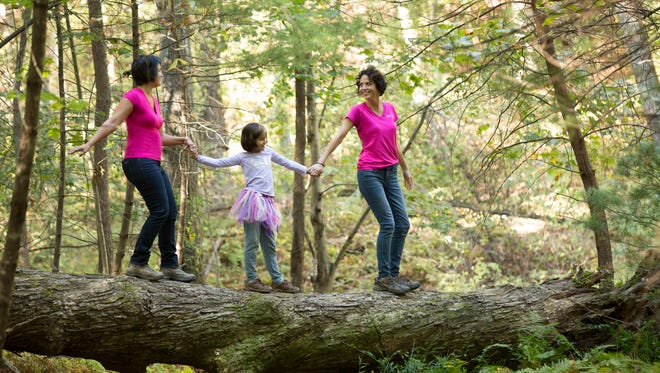 Karen Chávez, right, her sister, Dawn, and niece Phoebe show their love of nature with a walk through the woods.