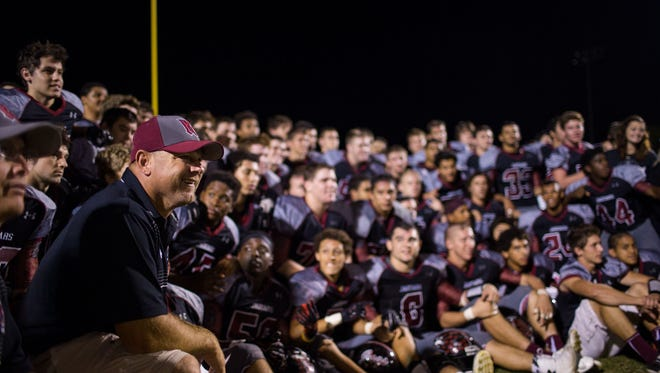 Desert Ridge head coach Jeremy Hathcock celebrates with his team after their win over Mountain View October 30, 2014 in Mesa, Ariz.