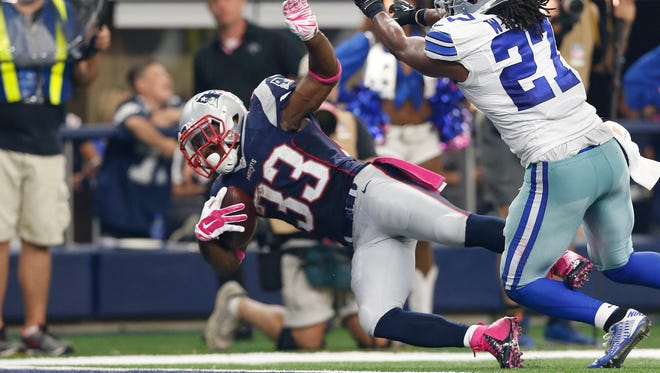 New England Patriots running back Dion lewis (33) scores a third quarter touchdown against Dallas Cowboys safety J.J. Wilcox (27) at AT&T Stadium.