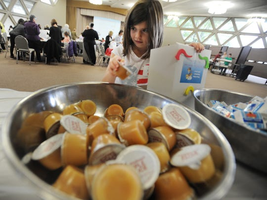 Alexa Cutler, 8, of Farmington Hills puts applesauce in a care package at Shaarey Zedek in Southfield on Sunday, part of Rosh Hashana activities and celebrations.