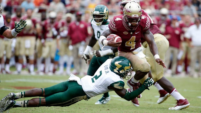 Sep 12, 2015; Tallahassee, FL, USA; Florida State Seminoles running back Dalvin Cook (4) tries to elude South Florida Bulls defensive back Jamie Byrd (2) at Doak Campbell Stadium. Florida State won 34-14. Mandatory Credit: Glenn Beil-USA TODAY Sports
