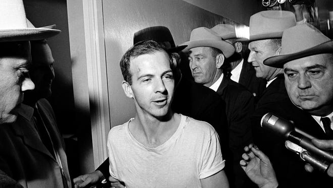 In this Nov. 23, 1963, file photo, surrounded by detectives, Lee Harvey Oswald talks to the media as he is led down a corridor of the Dallas police station for another round of questioning in connection with the assassination of U.S. President John F. Kennedy.