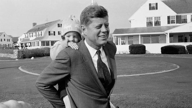In this Nov. 9, 1960 file photo, Caroline Kennedy gets a piggy-back ride from her father, Sen. John F. Kennedy, in Hyannis Port, Mass.