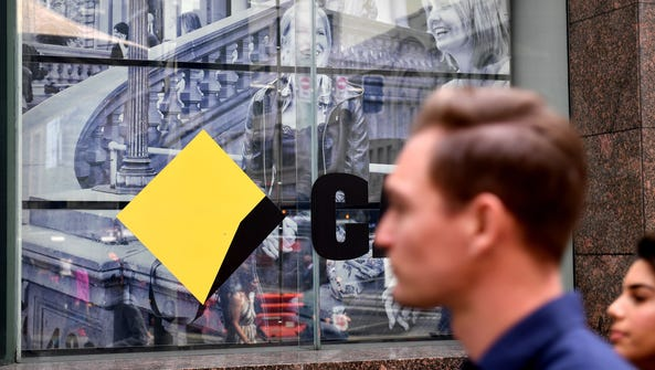 Pedestrians walk past a Commonwealth Bank sign in Sydney,