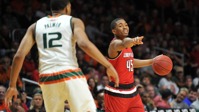Feb 27, 2016; Coral Gables, FL, USA; Louisville Cardinals guard Donovan Mitchell (45) dribbles the ball as Miami Hurricanes guard James Palmer (12) defends during the first half at BankUnited Center. Mandatory Credit: Steve Mitchell-USA TODAY Sports
