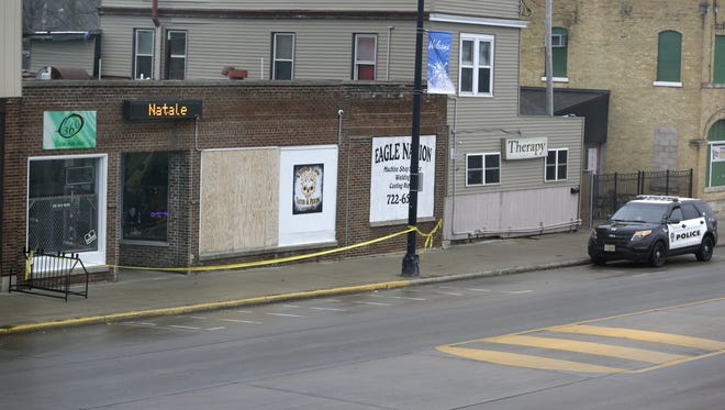 Crime scene tape remains in place at Eagle Nation Cycles on Main Street in Neenah, the site of Saturday's deadly standoff.