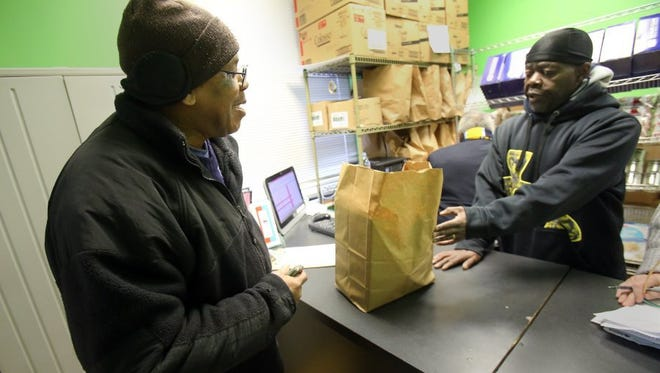 A client receive food, enough for three days, at the St. Patrick Catholic Church food pantry at 297 S. Fourth St. in Memphis on Feb. 10, 2016.