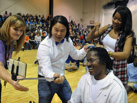 Samual Pak uses his phone to record himself cutting a dreadlock from Coach Russell Henry's hair. Henry raised $2,300 by letting his 34-inch braids be cut to raise money for a memorial bench for slain student Lauren Landavazo.