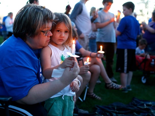 In this Monday, May 7, 2018 photo, Julie Borton, left, shares a moment with Violet Hanna, 4, during a candlelight vigil for missing 16-year-old Jake Wilson at Wolf Creek Landing in La Porte City, Iowa. The vigil was to show support for Jake's family and friends and a reminder that he is in everyone's thoughts as the search and investigation continues.