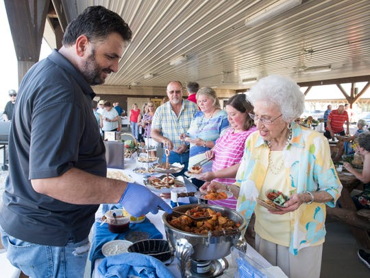 Doros Hadjisavva, the owner of Acropolis Greek Restaurant, describes Ttavas, a pork stew, to Mildred Conaway during the Farm to Table event held at the Henderson County Fairgrounds Monday, July 16, 2018.
