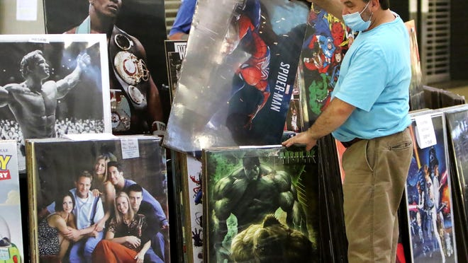 Poster Guy Brad Mechum sets up his table, Thursday, July 9, 2020, at the Sports Collectibles Show in Central Mall. The show continues through July 12, 2020, and includes more than 40 tables of sports-related items ranging from vintage to today's stars.